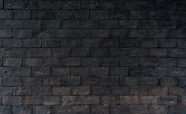 Black and brown brick wall rough texture background. dark brick wall for grieving emotional. exterior architecture. Premium Photo