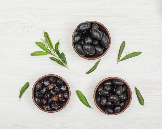 Black and brown olives in a clay bowls with olive tree branch and leaves top view on white wood Free Photo