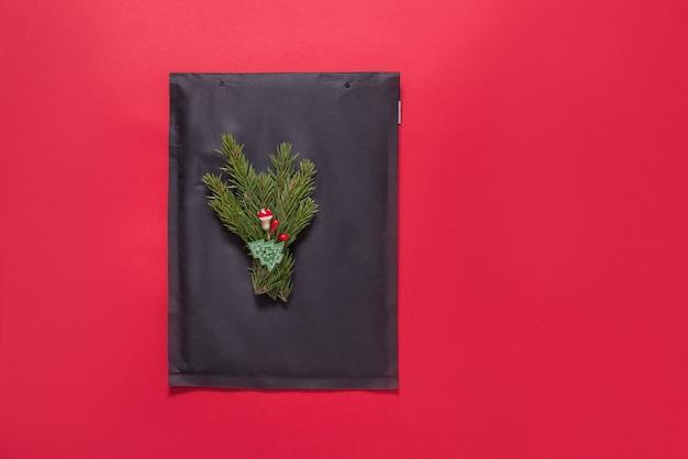 赤のクリスマスツリーの飾りで飾られた黒い泡の封筒 Premium写真