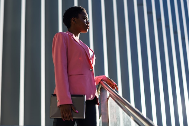 Black businesswoman standing near business office building. Premium Photo