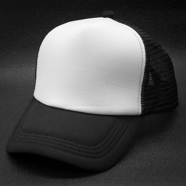 Black cap and white surface on dark background. fashion hat for design. Premium Photo