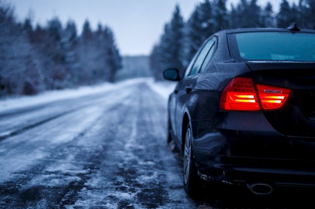 Черный автомобиль на обледенелой дороге в окружении деревьев, покрытых снегом Бесплатные Фотографии