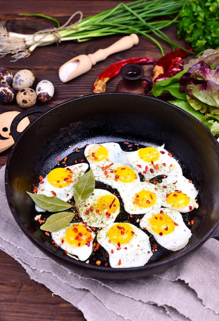 Black cast-iron frying pan with fried quail eggs Premium Photo