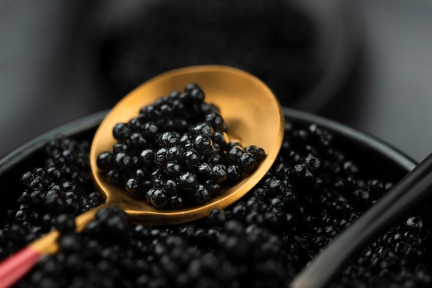 Black caviar in golden spoon Free Photo