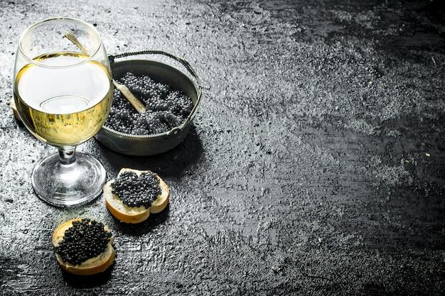 サンドイッチとワインの入ったボウルに黒キャビア。黒の素朴なテーブルの上 Premium写真