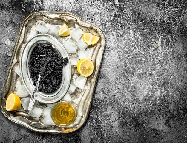 素朴なテーブルの上に白ワインとレモンのスライスと黒キャビア。 Premium写真