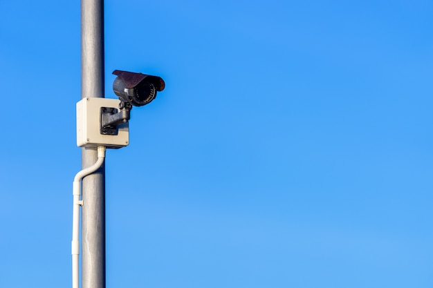 Black cctv camera on bronze metal pole with white plastic tube for wires and clear blue sky Premium Photo