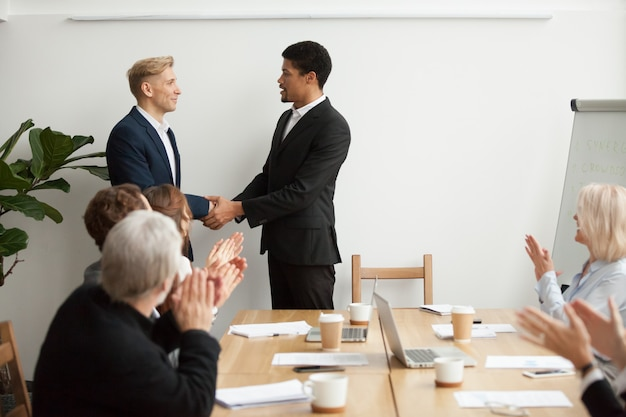 Black ceo and white businessman shaking hands at group meeting Free Photo
