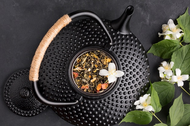 Black ceramic teapot with dry herb ingredient and white flower twig on black background Free Photo