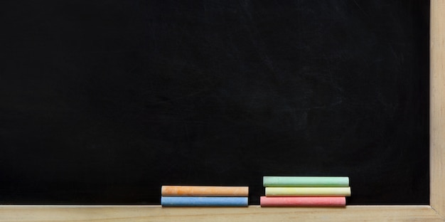 Black chalk board and colorful chalks Premium Photo
