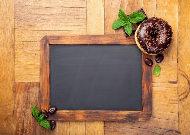 Black chalkboard with chocolate glazed donut Premium Photo