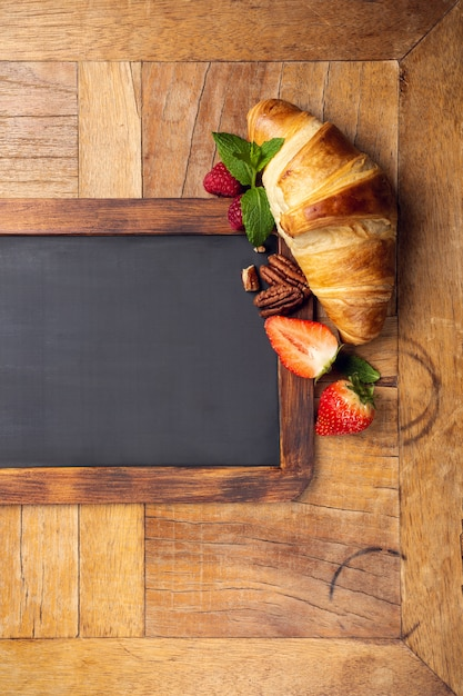 Black chalkboard with croissant and berries Premium Photo