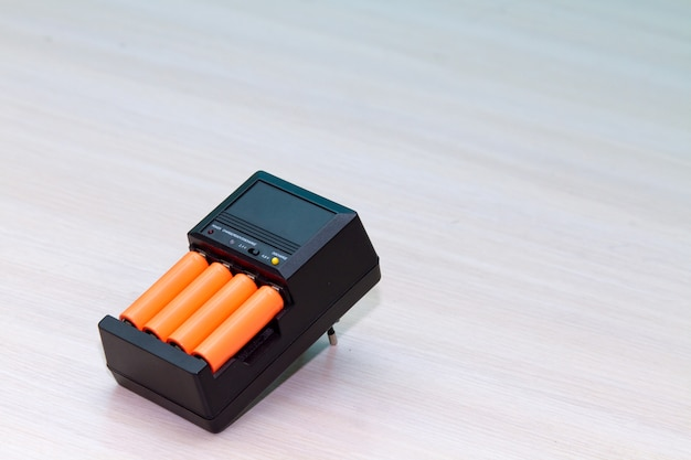 Black charger with orange aaa battery Premium Photo