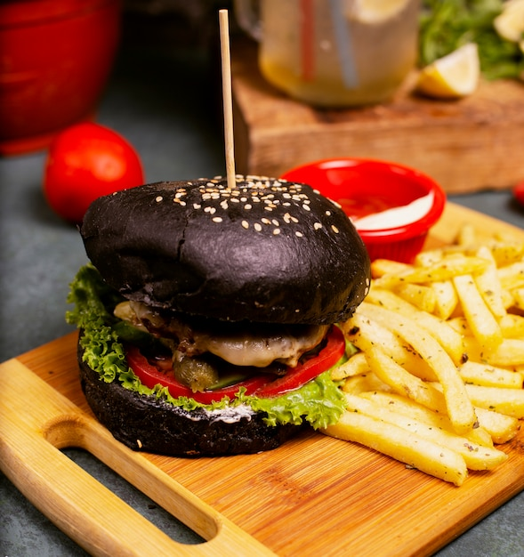 Black chocolate pan beef cheese burger with vegetables fast food, french fries and ketchup Free Photo