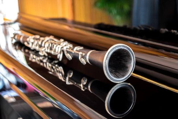 Черный кларнет, лежащий на закрытии рояля Бесплатные Фотографии