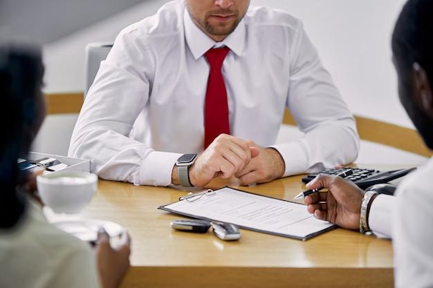 흑인 고객은 세일즈맨과 테이블에 앉아있는 동안 계약을 체결 프리미엄 사진