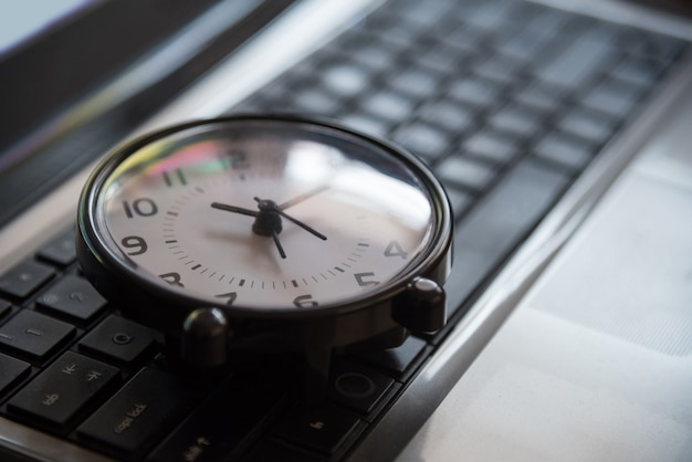 Black clock lay on keyboard time metaphor concept in dark low key tone Premium Photo