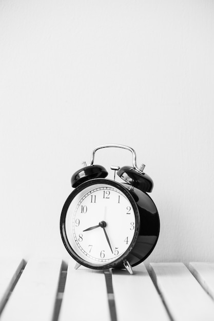 Black clock on table with copy space Free Photo