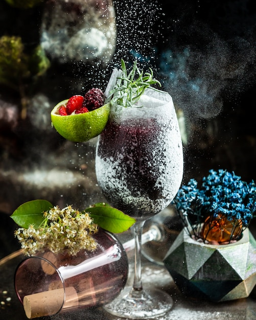 Black cocktail with vanilla powder and berries. Free Photo