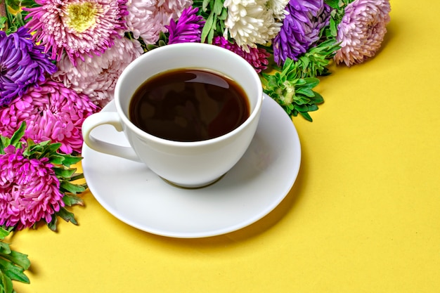 Black coffee americano in a white cup and flowers asters on yellow background flat lay Premium Photo