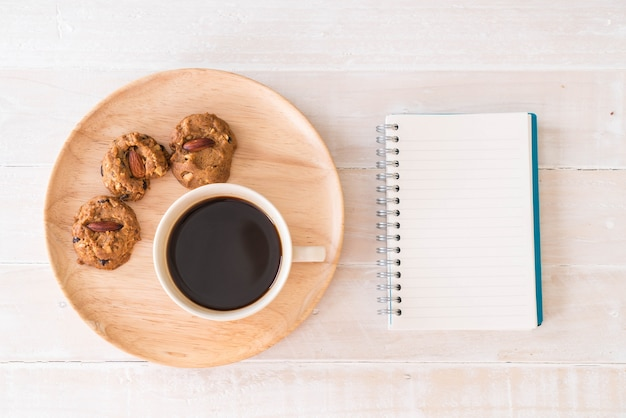 black coffee and cookies with laptop and note book Free Photo