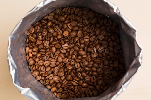 Черный кофе в зернах на бежевом фоне Бесплатные Фотографии