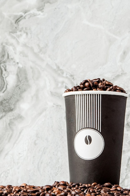 Black coffee in cup and coffee beans on marble background. top view, space for text. Premium Photo