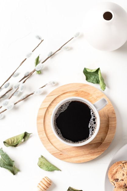 Black coffee in a cup and leaves on a white table Free Photo