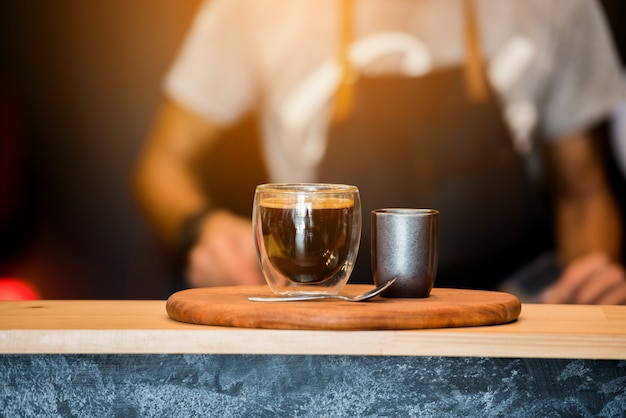 Black coffee cup on wooden table and coffee barista .film effect. Premium Photo