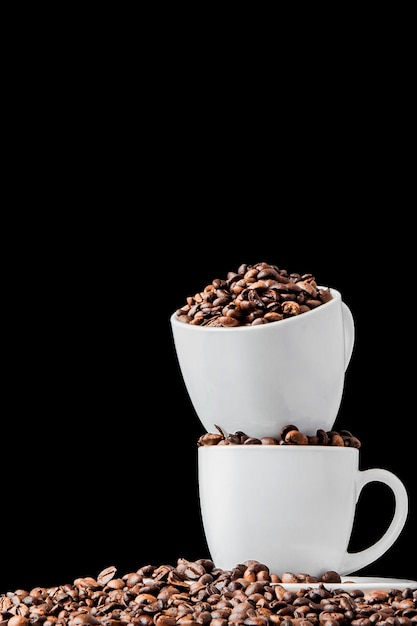 Black coffee in white cup and coffee beans on black background. top view, space for text. Premium Photo