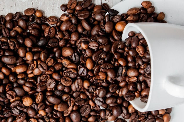 Black coffee in white cup and coffee beans on light wooden background. top view, space for text. Premium Photo