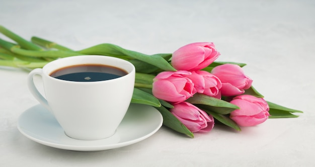 Black coffee in white cup and tulips. Premium Photo