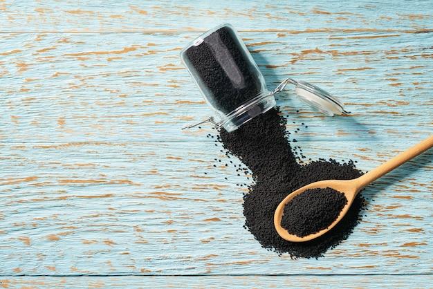 ガラスの瓶から木のスプーンに黒いクミンの種を注ぐ Premium写真