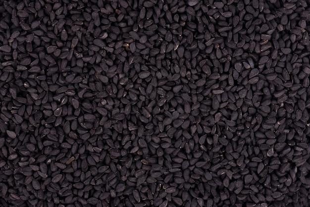 黒クミンの種。ニゲラ・サティバ。クローズアップの背景。 Premium写真