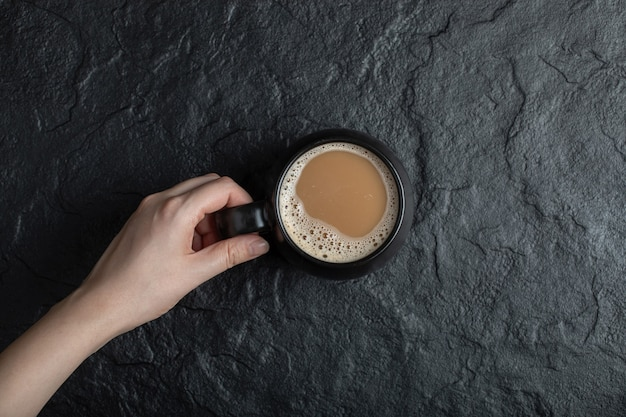 A black cup of coffee on black. Free Photo