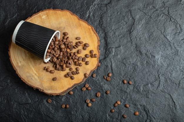 Una tazza nera piena di chicchi di caffè sulla tavola di legno. Foto Gratuite