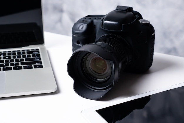 A black digital camera, a tablet and a computer laptop on a table. Premium Photo