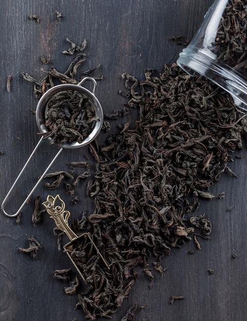 ストレーナー、瓶、スクープの木製の表面に黒の乾燥茶を置きます。 無料写真