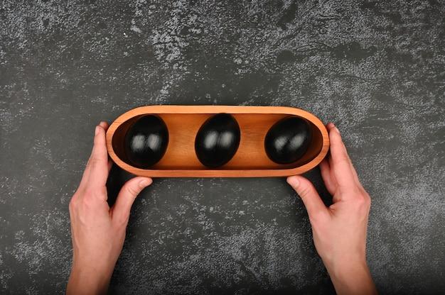手の中の黒い卵。フラット横たわっていた。ブラックイースター。 3つの黒い卵 Premium写真
