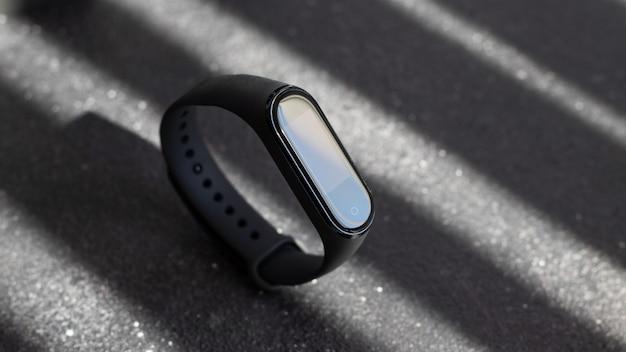 織り目加工の黒い表面に黒い電子時計とスマートフィットネストラッカー Premium写真