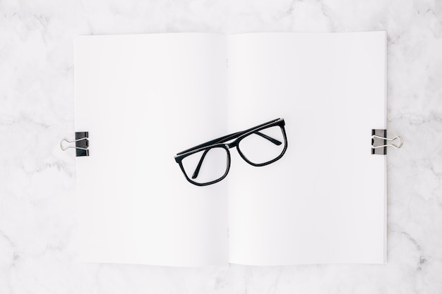 Black eyeglass over the white paper attach with two bulldog clips on marble backdrop Free Photo