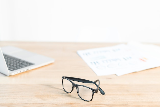 Black eyeglasses in front of laptop and graph on wooden desk Free Photo