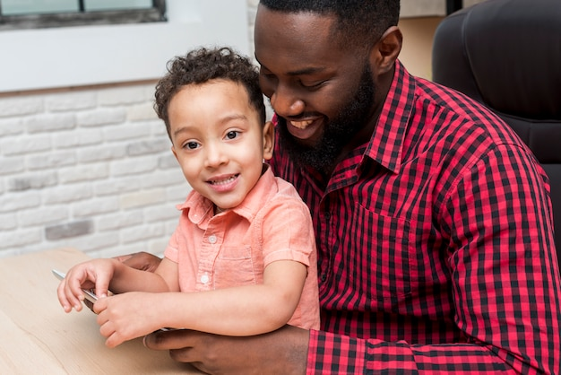 Black father and cute son using tablet Free Photo