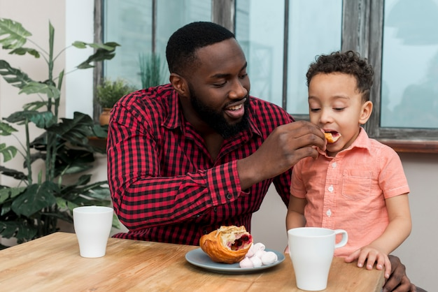 Black father feeding little son with croissant Free Photo