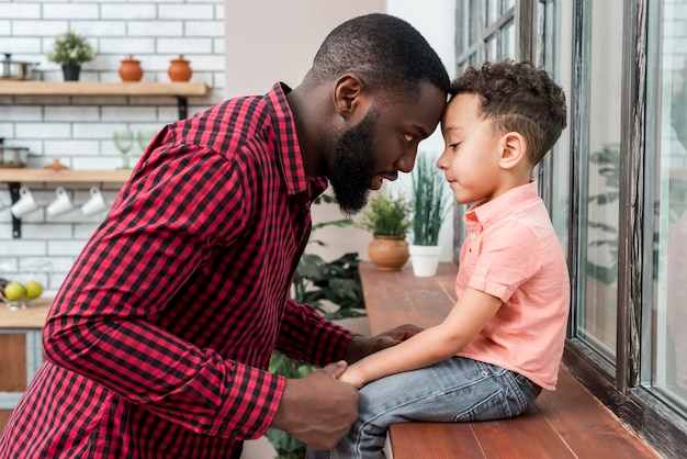 Black father holding hand of son on window sill Free Photo
