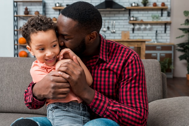 Black father hugging son on couch Free Photo