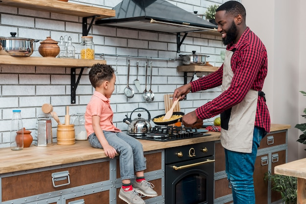 Black father and son cooking in kitchen Free Photo