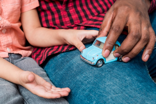 Black father and son playing with small toy car Free Photo