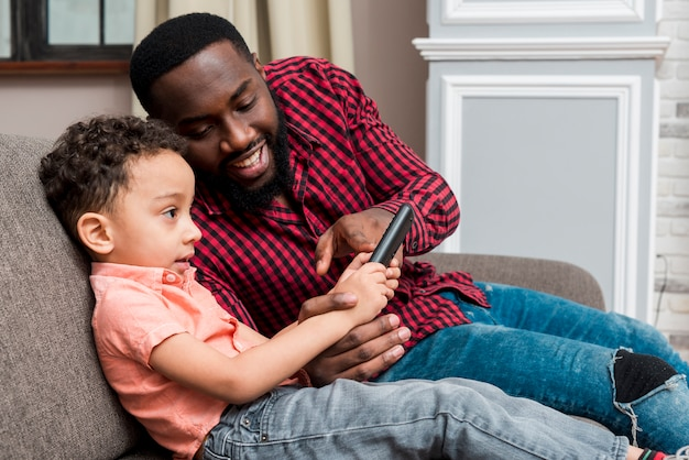 Black father and son using smartphone on couch Free Photo