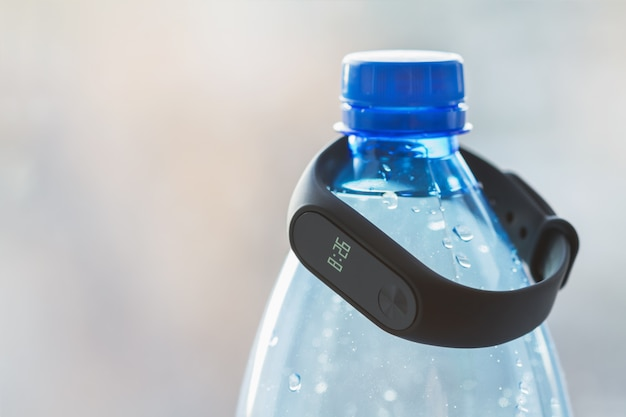 Black fitness tracker on a blue bottle of mineral water. Premium Photo